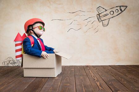 Szczęśliwe dziecko bawiące się w domu. Śmieszne dziecko siedzi w tekturowym pudełku. Marzenie z dzieciństwa, wolność i koncepcja zwycięzcy