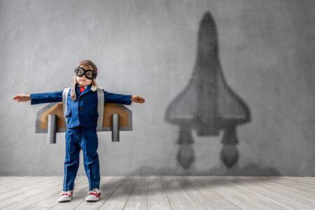 Niño feliz quiere volar. El niño divertido sueña con convertirse en un cohete. Concepto de imaginación, libertad y motivación.