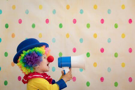 Lustiger Kinderclown gegen Tupfenhintergrund. Porträt des glücklichen Kindes im Studio. 1. Aprilscherz Konzept