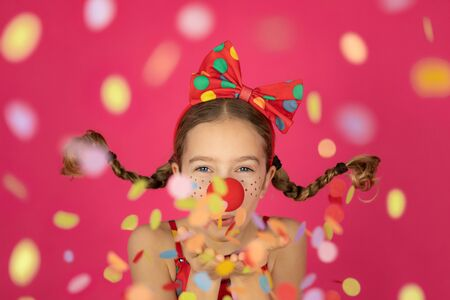 Funny girl clown against pink background. Happy child playing indoor. 1 April Fool's day and carnival holiday concept
