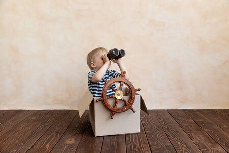 Un enfant heureux rêve de devenir capitaine. Enfant s'amusant à la maison. Garçon portant une chemise rayée jouant dans une boîte en carton. Concept de vacances et de voyage d'été. Rêve et imaginaire