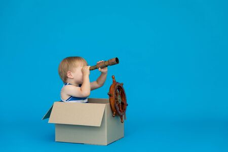 Happy child dreams of becoming a captain. Kid having fun against blue background. Boy wearing striped shirt playing in cardboard box. Summer vacation and travel concept. Dream and imagination