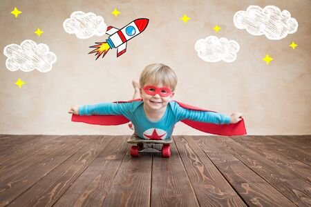 Portrait of super hero on the skateboard. Happy child playing at home. Superhero kid having fun. Success, creative and start up concept Stock Photo