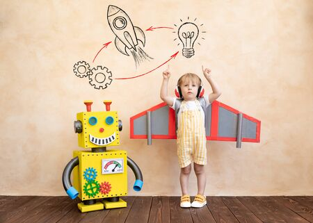 Happy child with cardboard wings. Funny kid playing with toy handmade robot. Success, creative and innovation technology concept