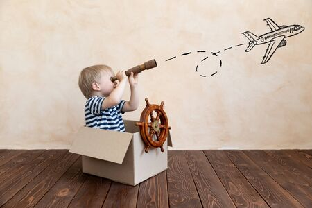 Happy child dreams of becoming a captain. Kid having fun at home. Boy wearing striped shirt playing in cardboard box. Summer vacation and travel concept. Dream and imagination