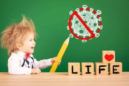 Child drawing sign stop coronavirus covid-19. Happy kid against green chalkboard. Safe life concept.