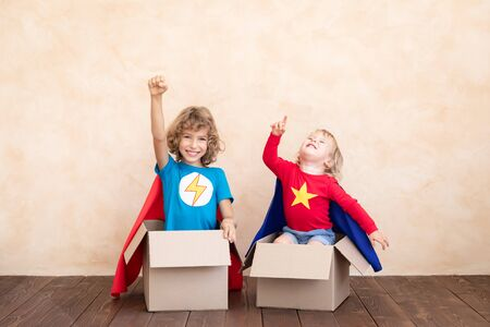 Superheroes children playing in cardboard box.