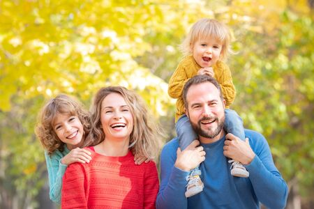 Happy family having fun outdoor in autumn park. Children and parents against yellow blurred leaves background