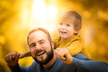 Happy family having fun outdoor in autumn park. Father and son against yellow blurred leaves background 版權商用圖片
