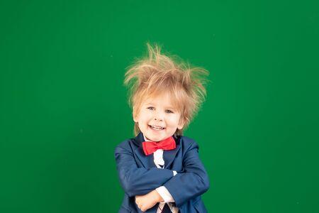 Happy kid against green chalkboard. 免版税图像