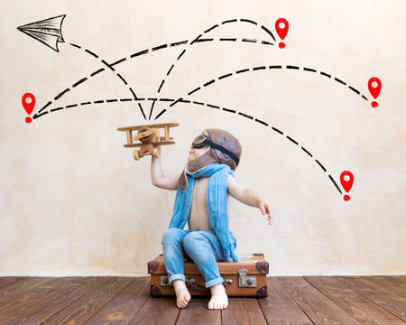 Happy child playing with vintage wooden airplane. Kid having fun at home. Imagination and freedom concept