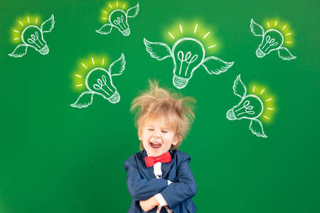 Be strong! Happy child in class. Smiling kid against green chalkboard. Portrait of student indoor. Imagination and dream concept. Back to school