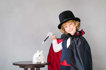 Child magician with cute rabbit. Happy kid playing at home. Imagination and magic trick concept