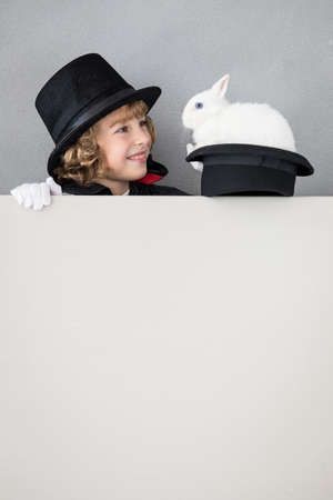 Child magician with rabbit hiding behind banner blank. Happy kid holding cardboard background with copy space