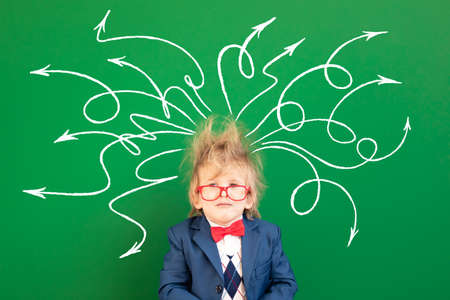Bright idea! Sad child student in class. Kid against green chalkboard. Online education and e-learning concept. Back to school 免版税图像