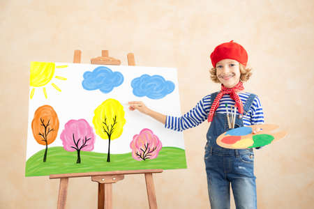 Artist child painting the picture on canvas. Happy kid pretend to be painter. Imagination and childhood dream concept