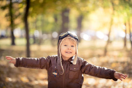 Happy child having fun outdoor in autumn park. Kid pilot playing against yellow blurred leaves background