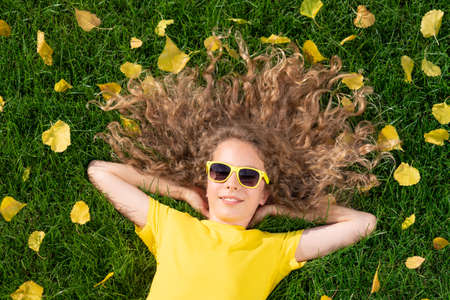 Beautiful girl lying on lawn with yellow leaves in autumn park. Happy child having fun outdoor.