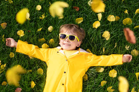 Top view portrait of happy child having fun outdoor in autumn park. Smiling kid lying on leaves against yellow blurred background