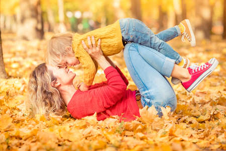 Happy family having fun outdoor in autumn park. People against yellow blurred leaves background