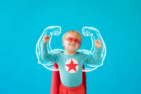 Portrait of superhero child. Super hero kid against blue background. Success and winner concept