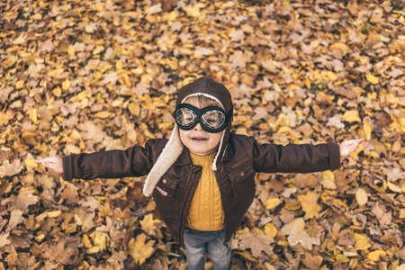 Happy child having fun outdoor in autumn park. Kid pilot playing against yellow blurred leaves background. Top view portrait