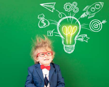 Bright idea! Funny child student in class. Happy kid against green chalkboard. Online education and e-learning concept. Back to school