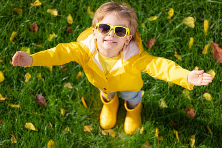 Top view portrait of happy child having fun outdoor in autumn park. Smiling kid standing on green grass against yellow leaves blurred background
