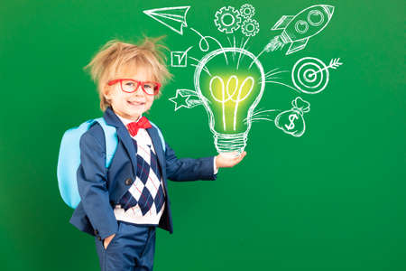 Bright idea! Funny child student with backpack in class. Happy kid against green chalkboard. Online education and e-learning concept. Back to school