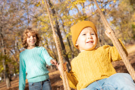 Happy children having fun outdoor in autumn park. Kids playing on swing against yellow blurred leaves background. Freedom and carefree concept