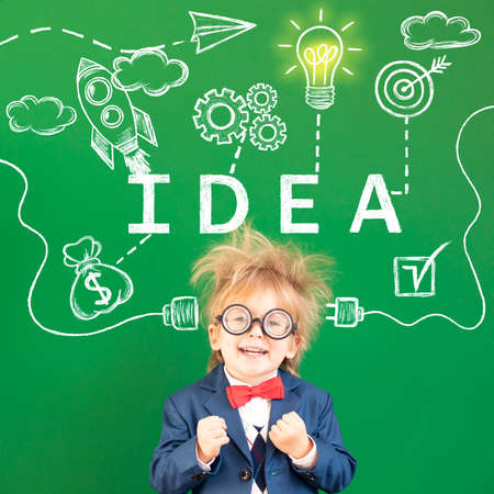 Bright idea! Strong nerd in class. Happy geek against green chalkboard. Portrait of smiling child. Kid having fun. Imagination and dream concept. Back to school