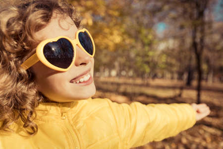 Happy child having fun outdoor in autumn park. Smiling girl against yellow blurred leaves background