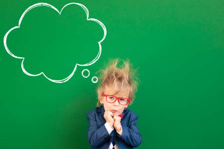Afraid child student in class. Sad kid against green chalkboard. Online education and e-learning concept. Back to school