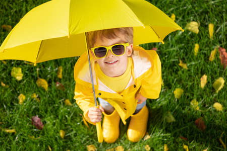 Top view portrait of happy child with umbrella outdoor in autumn park. Smiling kid standing on green grass against yellow leaves blurred background 免版税图像