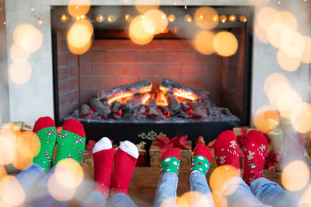 Happy family with children near fireplace at Christmas. Feet wearing Xmas socks. Winter holiday concept