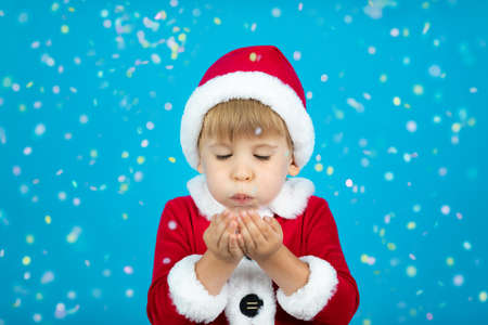 Happy child wearing Santa Claus costume. Kid blowing confetti against blue background. Christmas holiday concept