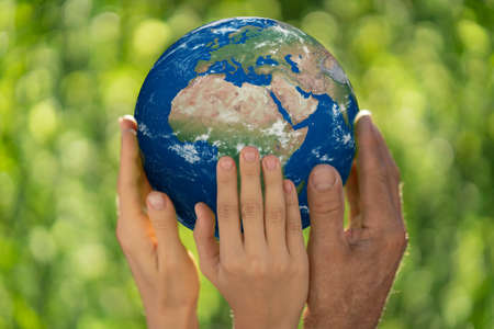 Family holding 3D planet in hands against green blurred background. Earth day spring holiday concept.
