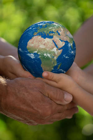 Family holding 3D planet in hands against green blurred background. Earth day spring holiday concept. Stockfoto
