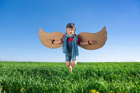 Happy child playing with toy wings against blue sky background. Kid having fun outdoor in spring green field. Imagination and children dream concept