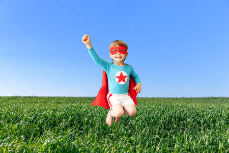 Happy superhero child jumping against blue sky. Super hero kid having fun in spring green field outdoor. Freedom and imagination concept Foto de archivo