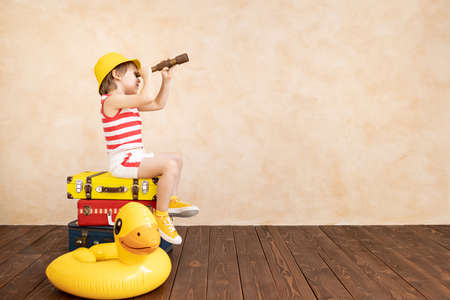 Happy child playing at home. Smiling kid dreaming about summer vacation and travel. Imagination and freedom concept