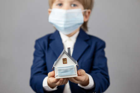 Child holding model house wearing protective medical mask in hands. Business during coronavirus COVID-19 pandemic concept Foto de archivo