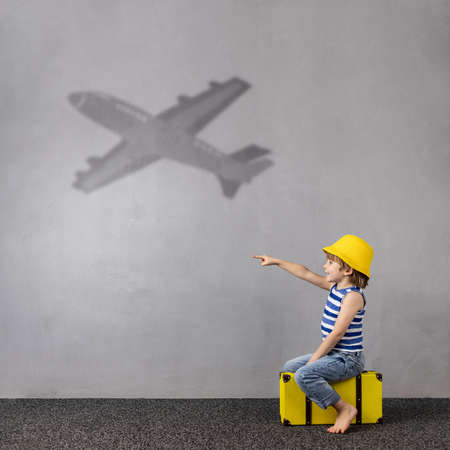 Happy child dreaming about travel. Summer vacation concept Foto de archivo