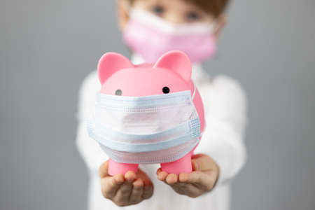 Child holding piggybank wearing protective medical mask in hands. Business during coronavirus COVID-19 pandemic concept