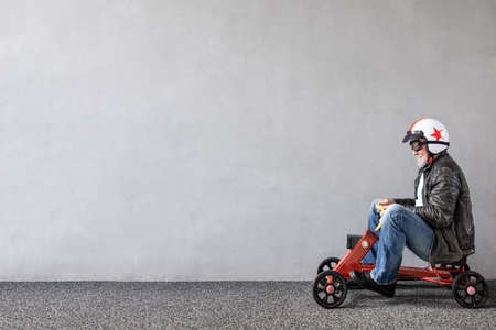 Senior man riding toy car. Full length portrait of funny businessman against concrete wall with copy space. Business start up concept