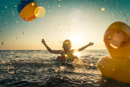 Happy child having fun on summer vacation. Kid playing with rubber duck and ball in the sea. Healthy lifestyle concept. Spring break! Foto de archivo