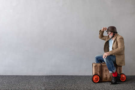 Senior man sitting on vintage suitcase. Full length portrait of funny businessman against concrete wall with copy space. Business start up concept