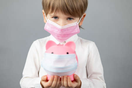 Child holding piggybank wearing protective medical mask in hands. Foto de archivo