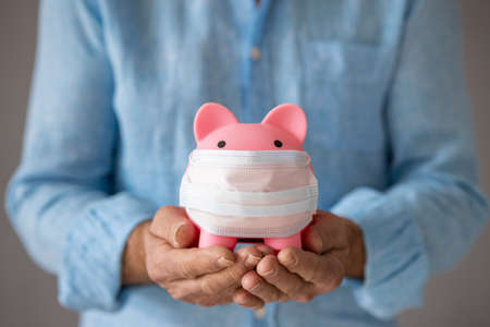 Senior businessman holding piggybank wearing protective medical mask in hands.