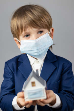Child holding model house wearing protective medical mask in hands.